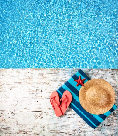 Photo pour Concept of summer accessories on wood with blue water as background - image libre de droit