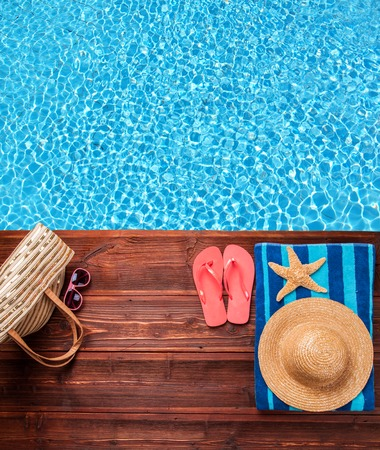 Foto de Concept of summer accessories on wood with blue water as background - Imagen libre de derechos