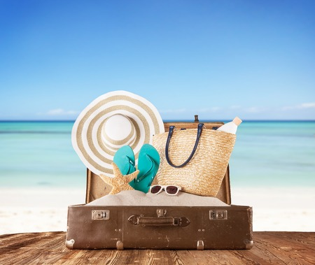 Photo pour Concept of summer travelling with old suitcase and accessories  Blur beach on background - image libre de droit