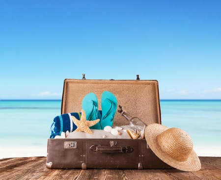 Foto de Concept of summer travelling with old suitcase and accessories  Blur beach on background - Imagen libre de derechos