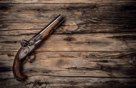 Very old hand gun on wooden planks, shot from upper view