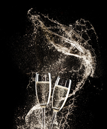 Foto de Glasses of champagne with splash, isolated on black background - Imagen libre de derechos