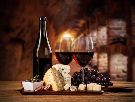 Foto de Various kind of cheese with red wine in cellar - Imagen libre de derechos