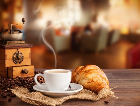 Foto de Coffee drink served with croissant on wooden table with blur cafeteria  - Imagen libre de derechos