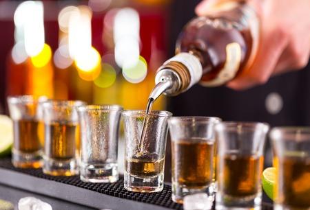 Foto de Barman pouring hard spirit into glasses in detail - Imagen libre de derechos