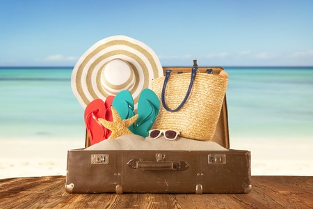 Photo pour Travel concept with old suitcase on wooden planks full of beach accessories. Placed on mole with sandy beach on background - image libre de droit