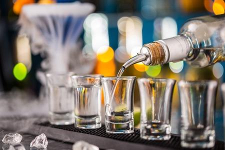 Photo pour Barman pouring hard spirit into glasses in detail - image libre de droit