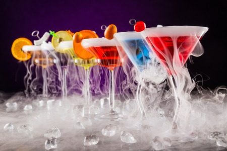 Foto de Martini drinks with dry ice smoke effect, served on bar counter with dark colored background - Imagen libre de derechos