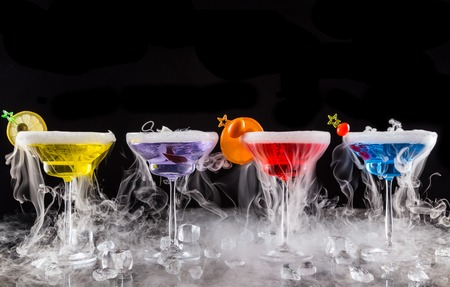 Foto de Martini drinks with dry ice smoke effect, served on bar counter with black background - Imagen libre de derechos