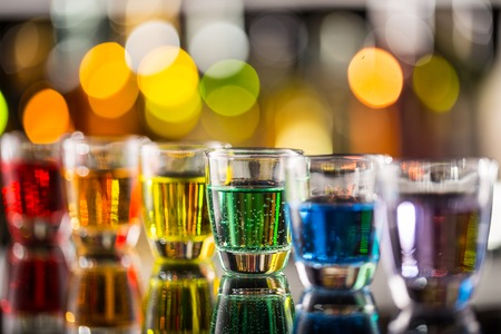 Photo for Variation of hard alcoholic shots served on bar counter. Blur bottles on background - Royalty Free Image