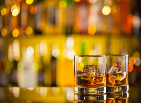 Photo for Whiskey drinks on bar counter with blur botles on backgorund - Royalty Free Image