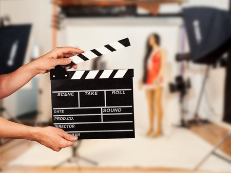 Photo for Man hands holding film clapper. Blur film studio on background - Royalty Free Image