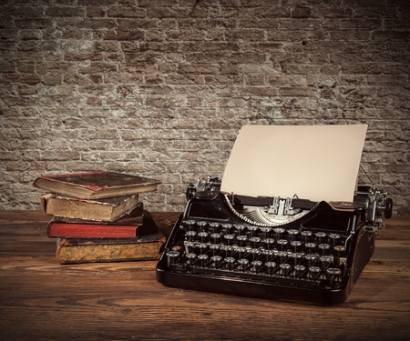 Photo pour Retro typewriter placed on wooden planks. Old brick wall as background with copyspace. - image libre de droit