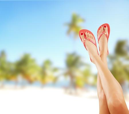 Photo pour Perfect female legs on sandy beach with sandals - image libre de droit