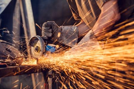 Photo pour Close-up of worker cutting metal with grinder. Sparks while grinding iron. Low depth of focus - image libre de droit