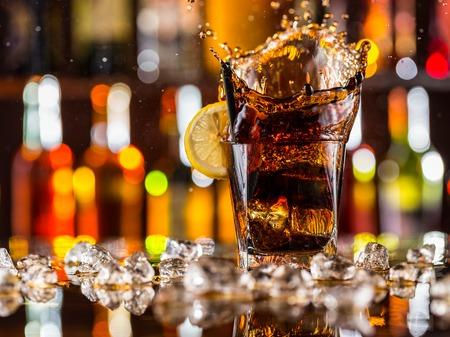 Foto de Glass of cola splashing out, placed on bar counter - Imagen libre de derechos