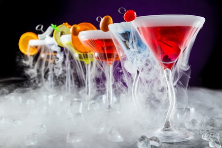 Photo for Martini drinks with dry ice smoke effect, served on bar counter with dark colored background - Royalty Free Image