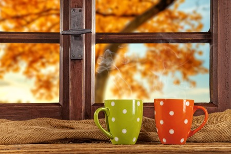 Photo pour Vintage wooden window overlook autumn trees, shot from cottage interior with cups of tea - image libre de droit