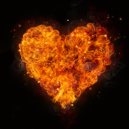 Foto de Hot fires flames in heart shape, isolated on black background - Imagen libre de derechos