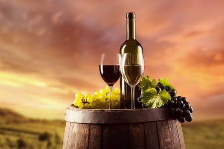 Photo pour Red and white wine bottle and glass on wooden keg. Vineyard on background - image libre de droit