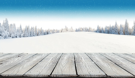 Photo pour Winter background with pile of snow and blur landscape. Empty wooden planks on foreground. Copyspace for text - image libre de droit