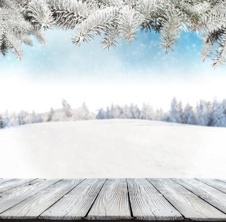 Foto de Winter background with pile of snow and blur landscape. Empty wooden planks on foreground. Copyspace for text - Imagen libre de derechos