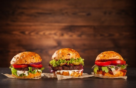Photo pour Delicious hamburgers served on wooden planks - image libre de droit