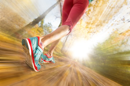 Foto de Close up of feet of female runner running in autumn leaves. Fitness exercise. Blur motion - Imagen libre de derechos