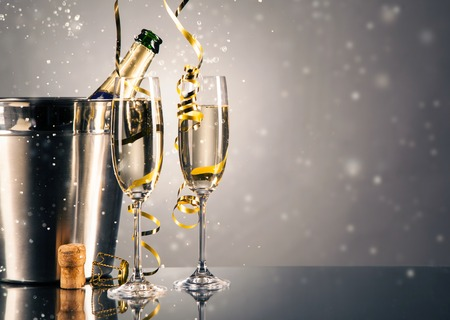 Foto de Pair glass of champagne with bottle in metal container. New Year celebration theme with blur spots of bubbles - Imagen libre de derechos