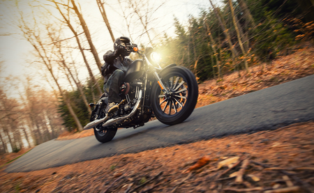 Foto de Young man riding black chopper on road in forest - Imagen libre de derechos