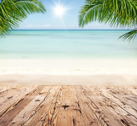 Foto de Empty wooden planks with blur beach on background, can be used for product placement, Palm leaves on foreground - Imagen libre de derechos