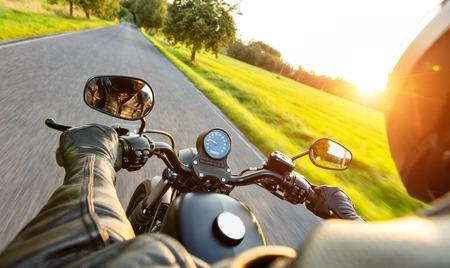 Foto de Motorcycle driver riding on motorway in beautiful sunset light. Shot from pillion driver view - Imagen libre de derechos