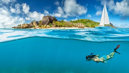 Photo pour Young woman snorkling next to tropical island. Anchoring catamaran on background - image libre de droit