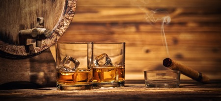 Photo for Two glasses of whiskey with ice cubes served on wooden planks with keg. Vintage countertop with highlight and glasses of hard liquor - Royalty Free Image