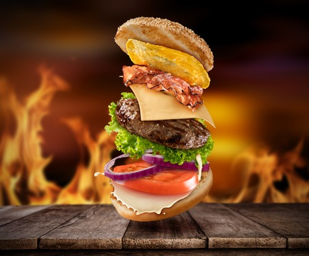 Photo pour Maxi hamburger with flying ingredients placed on wooden planks with flames on background. Copyspace for text, high resolution image - image libre de droit