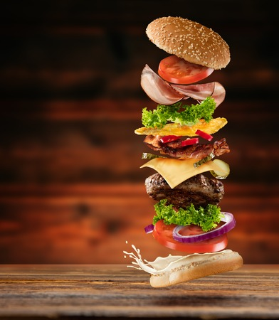 Photo pour Maxi hamburger with flying ingredients placed on wooden planks. Copyspace for text, high resolution image - image libre de droit