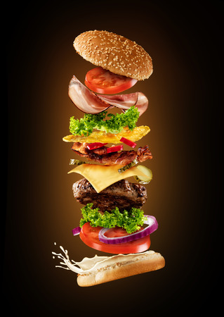 Photo for Maxi hamburger with flying ingredients isolated on dark background. High resolution image - Royalty Free Image
