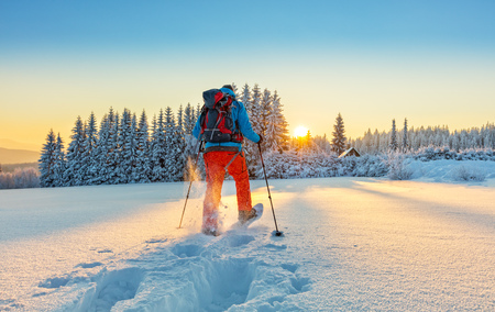 Photo for Snowshoe walker running in powder snow with beautiful sunrise light. Outdoor winter activity and healthy lifestyle - Royalty Free Image