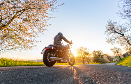 Photo for Back view of motorcycle driver driving in beautiful sunset - Royalty Free Image