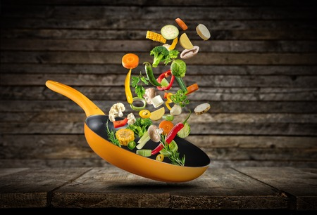 Photo pour Fresh vegetables flying into a pan, placed on wooden planks - image libre de droit