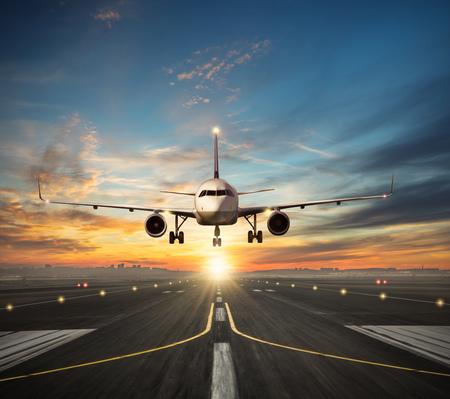Foto de Passengers airplane landing to airport runway in beautiful sunset light, silhouette of modern city on background - Imagen libre de derechos