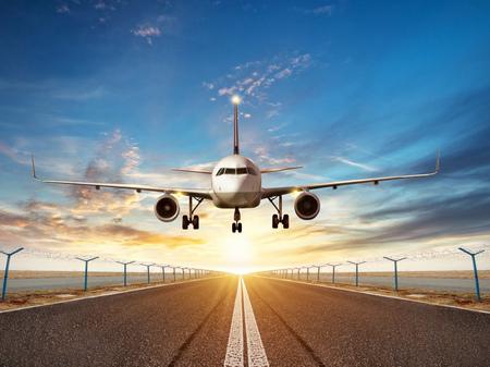 Foto de Passengers airplane landing to airport runway in beautiful sunset light - Imagen libre de derechos