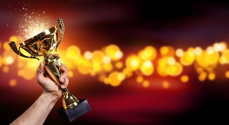 Photo for Man holding up a gold trophy cup with abstract shiny background, copy space for text - Royalty Free Image