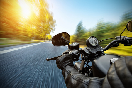 Foto de Close-up of motorbiker riding on empty road in forest with sunrise light, concept of speed and travel in nature - Imagen libre de derechos