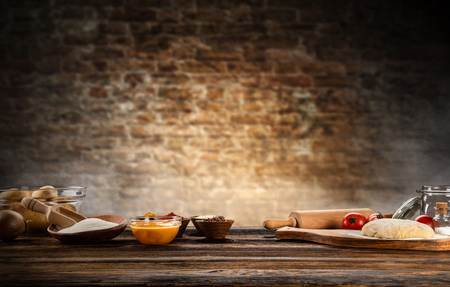 Foto de Baking ingredients placed on wooden table, ready for cooking. Copyspace for text. Concept of food preparation, dark background. - Imagen libre de derechos