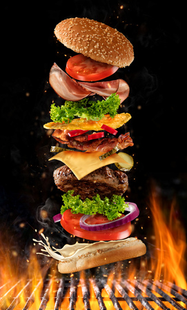 Foto de Flying burger ingredients above grill fire. Concept of low gravity motion and meal preparation. Isolated on black background - Imagen libre de derechos