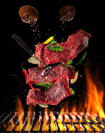 Foto de Flying pieces of raw steaks, with ingredients for cooking, barbecue grill with fire flames. Concept of food preparation in low gravity mode. Separated on smooth background - Imagen libre de derechos