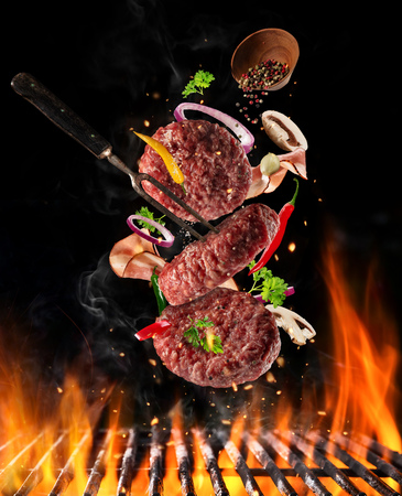 Photo pour Flying raw milled beef meat, with ingredients for cooking above grill fire. Freeze motion of cooking staff. Fork holding the meat. Concept of food preparation in low gravity mode. - image libre de droit