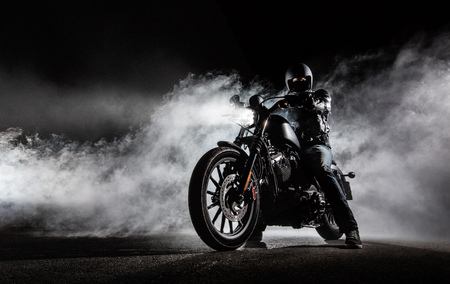 Foto de High power motorcycle chopper with man rider at night. Fog with backlights on background. - Imagen libre de derechos