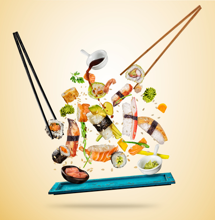 Foto per Flying sushi pieces served on wooden plate, separated on colored background. Many kinds of popular sushi food with chopsticks. Concept of flying asian dish with ingredients - Immagine Royalty Free
